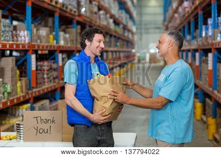 Portrait of volunteers are holding a grocery bag in a warehouse