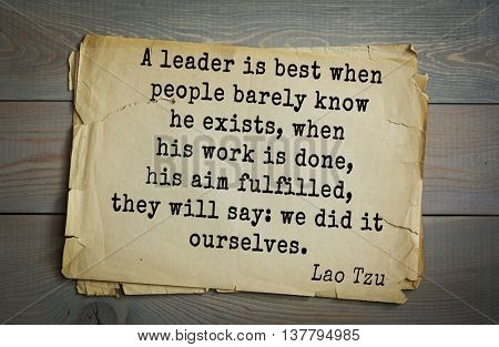 Ancient chinese philosopher Lao Tzu quote on old paper background. A leader is best when people barely know he exists, when his work is done, his aim fulfilled, they will say: we did it ourselves.