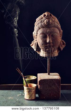 Buddha statue with incense sticks