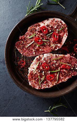 Marinated pork steaks in a ceramic dish