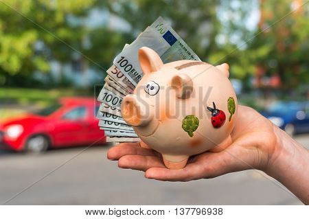 Salesman giving car keys to a new car owner who is paying all saving money from piggy bank on blurred background