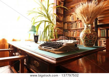 Old typewriter on wooden table in library