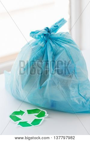 waste recycling, reuse, garbage disposal, environment and ecology concept - close up of rubbish bag with trash or garbage and green recycle symbol at home