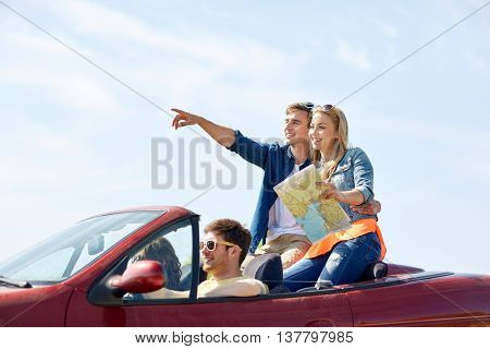 leisure, road trip, travel and people concept - happy friends with map driving in cabriolet car along country road and pointing finger to something ahead