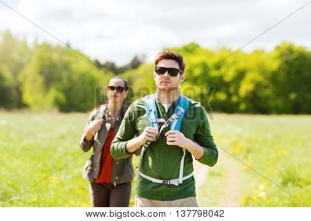 travel, hiking, backpacking, tourism and people concept - couple with backpacks walking along country road outdoors