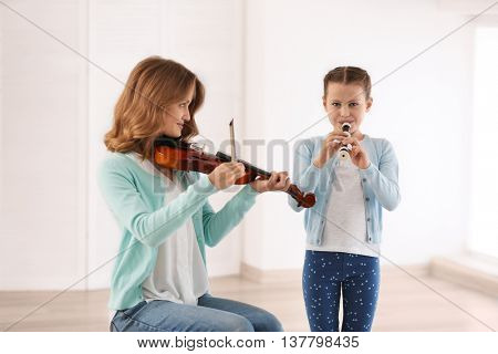 Two girls playing violin and flute on light background