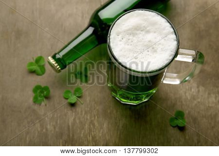 Glass of green beer with clover leaves and bottle on wooden background