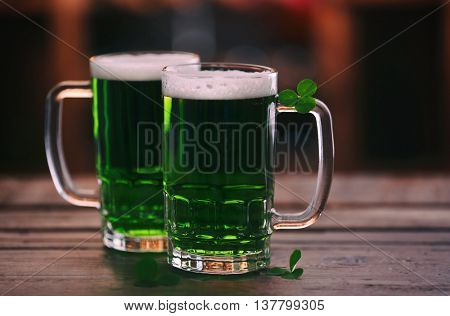Glasses of green beer with clover leaves on wooden table