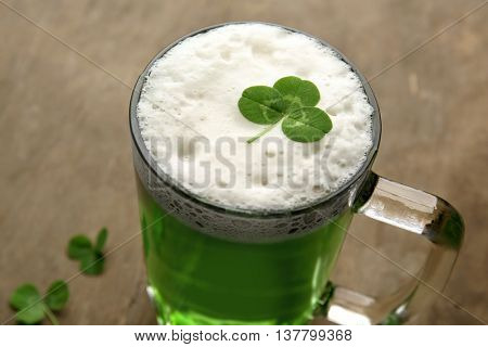 Glass of green beer with clover leaf on wooden background