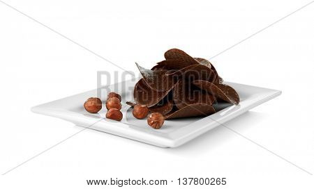 Chocolate chips and hazelnuts in plate on white background