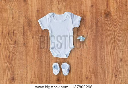baby clothes, babyhood, motherhood and object concept - close up of white bodysuit, bootees and soother for newborn boy on wooden table
