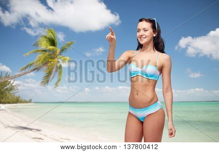 people, travel, tourism, swimwear and summer holidays concept - happy young woman in bikini swimsuit pointing finger to something imaginary over exotic tropical beach with palm trees background