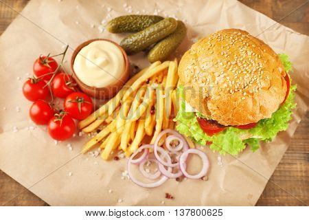 Hamburger with fries on wooden background