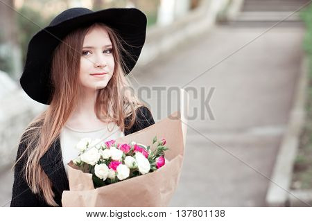 Beautiful teenage girl 14-16 year old holding flower in paper outdoors. Looking at camera.