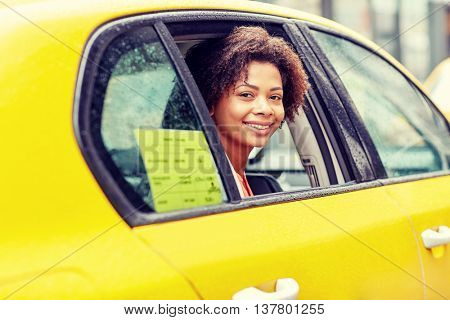 business trip, transportation and people concept - young smiling african american woman driving in taxi at city street