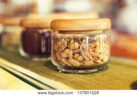 food, storage and eating concept - close up of jars with peanuts and spices at grocery