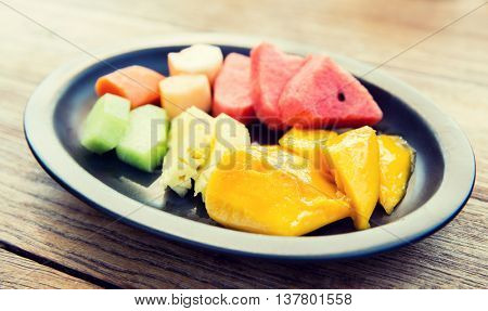cooking, kitchen and food concept - plate of fresh juicy fruits at asian restaurant or home