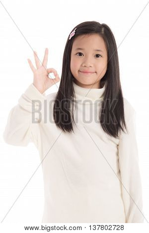 Cute asian girl in white turtleneck dress showing ok signwhite background isolated