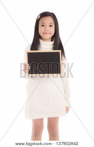 Cute asian girl in white turtleneck dress holding blackboard on white background isolated