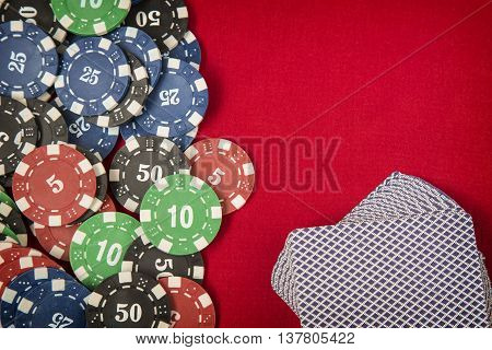 Gambling chips frame and card deck on red card table background