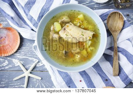 Fish soup with potato on the wooden table