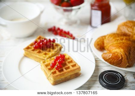 Waffles with red currant jam and berries on a white plate croissants orange juice and oat flakes oatmeal on the wooden background