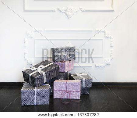Pink and gray gifts with bows on the floor by the wall