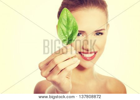 Beautiful woman with one green leaf.