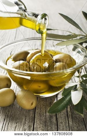 Bottle pouring virgin olive oil in a bowl with green olives close up