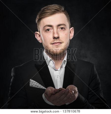 Businessman beggar in suit over dark background.