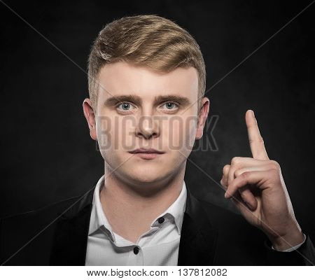 Idea. Young man shows finger up over darck background.