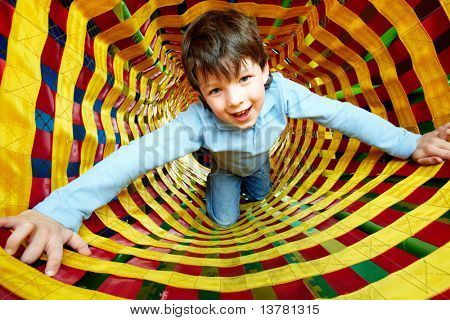 Happy lad looking at camera while having fun inside toy tunnel
