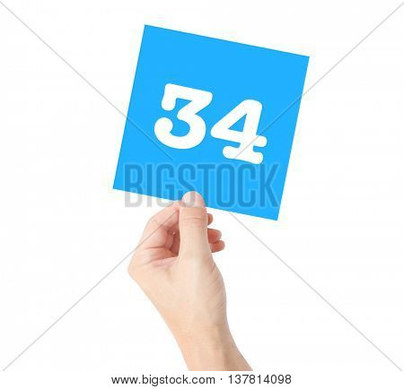 34 written on a card held by a hand