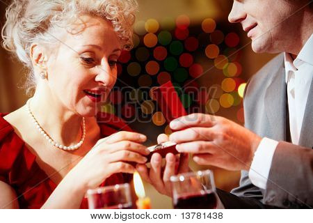 Image of beautiful woman looking into small open box before her being given by man