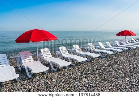 Two Parasol And Plastic Beach Chairs
