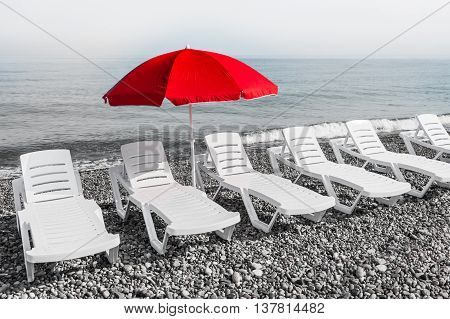 Red Sun Umbrella And Plastic Beach Beds