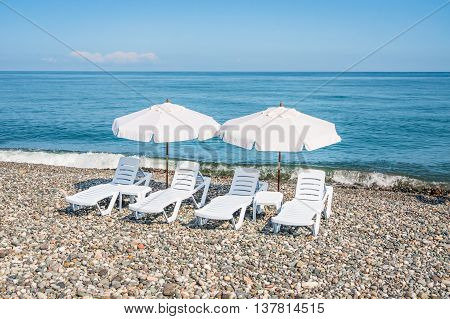 Four White Plastic Beach Chairs And Two White Parasols On The Be
