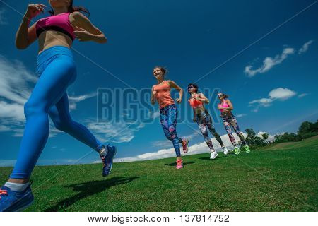 Morning running. Running athletes. Group of female runners on scamper.