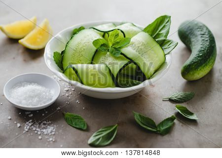Bowl of fresh cucumber and mint salad with sea salt and lemon