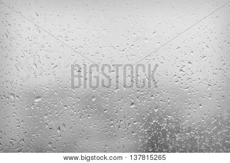 In the evening, the rain on the windowpane. Use as a background. Low depth of focus.