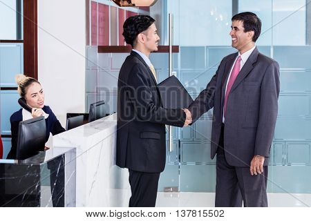 Indian business executive welcoming Asian associate in office lounge shaking hands