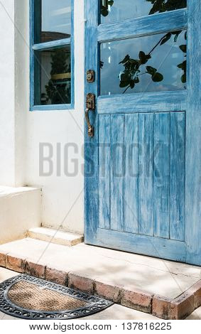 Blue wooden door with old doormat of the countryside house.