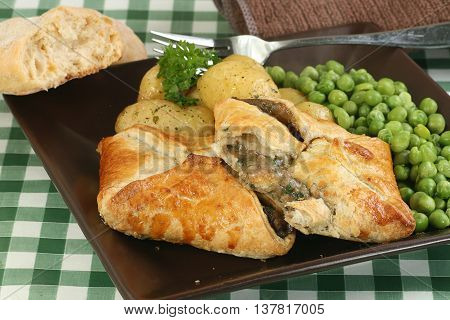 vegetarian food stilton and mushroom en croute with peas and new potatoes