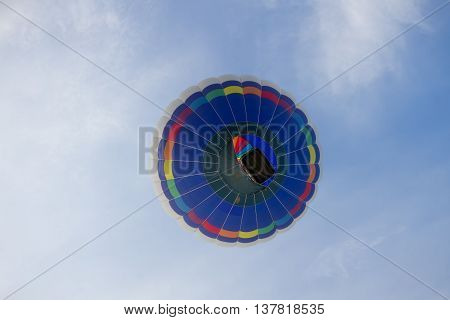 A colorful multi color hot air balloon floats among the clouds and the blue sky