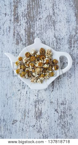 dried chamomile on a white wooden background