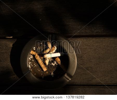 dark ash of smoking cigarette on wood background