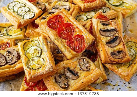 Puff pastry appetizers with vegetables, mushrooms, tomatoes, zucchini and cheese