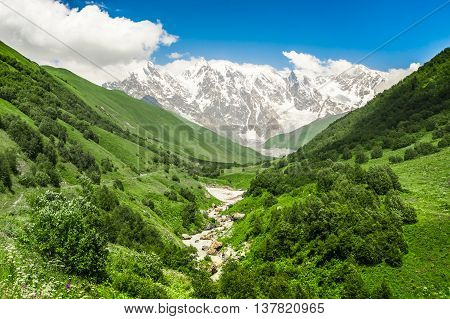 Mountain Stream And Snow-capped Mountains In Georgia