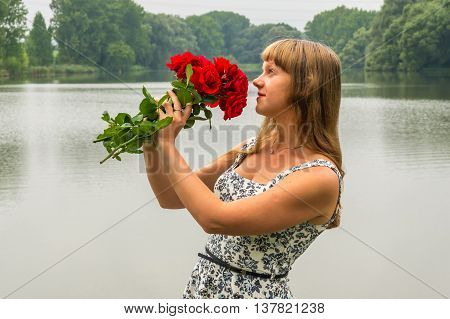 Young Lady By The Lake Holds A Roses