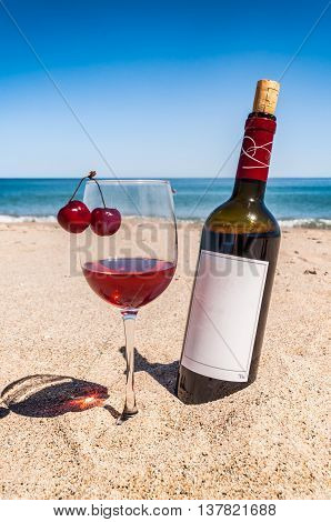 A bottle of wine and glass with cherries on the sand beach near sea